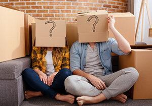 Moški in ženska sedita na tleh med gorami kartonskih škatel in imata vsak svojo prazno škatlo z narisanim vprašajem na glavi.