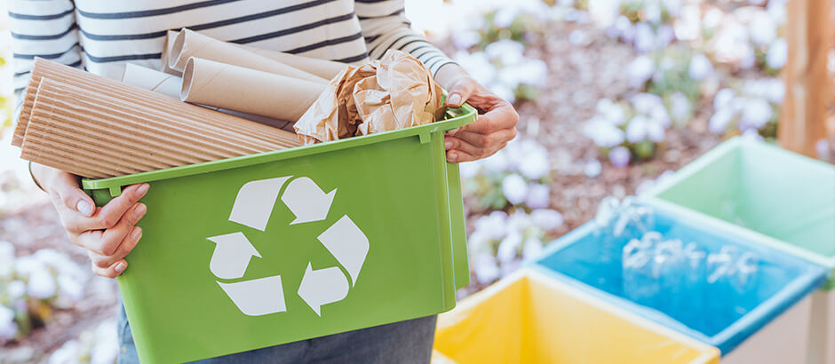 Ženska v rokah drži zelen plastičen zaboj s papirnatimi smetmi, ob strani pa so rumen, moder in zelen koš za smeti.