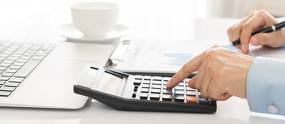 Moški z levo roko tipka na kalkulator, v desni pa drži svinčnik.