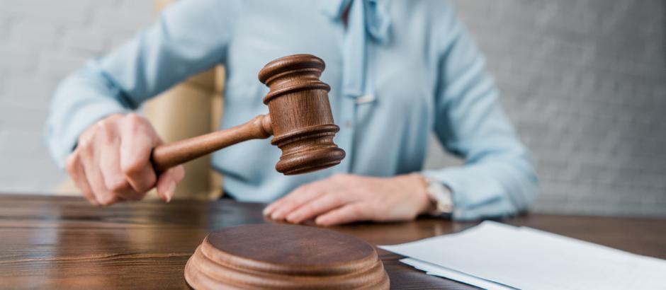 Ženska v sodni dvorani z lesenim sodniškim kladivom udarja ob mizo, s čimer simbolizira sprejetje nove uredbe.